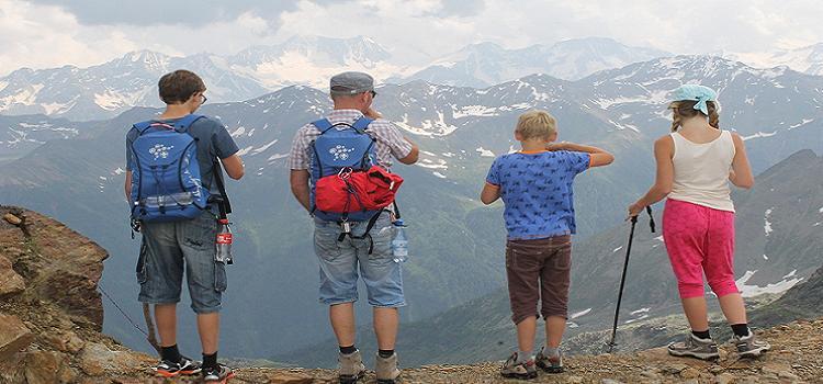 Drei Kinder und der Vater auf einem Wanderweg