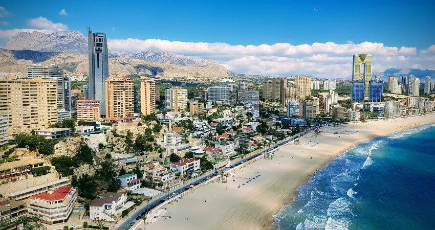 Langer Sandstrand und dahinter viele Gebäude und Hotels.