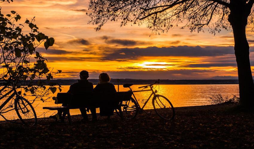 Ein Paar sitzt auf einer Bank am Bodensee und beobachtet den Sonnenuntergang.