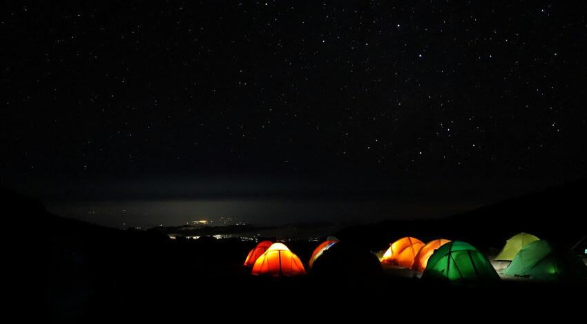 Beleuchtete Zelte in der dunklen Nacht mit vielen kleinen Sternen am Himmel.