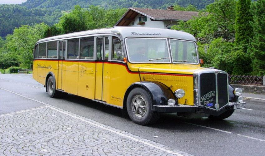Ein gelber Oldtimer Bus mit hell grauem Dach.