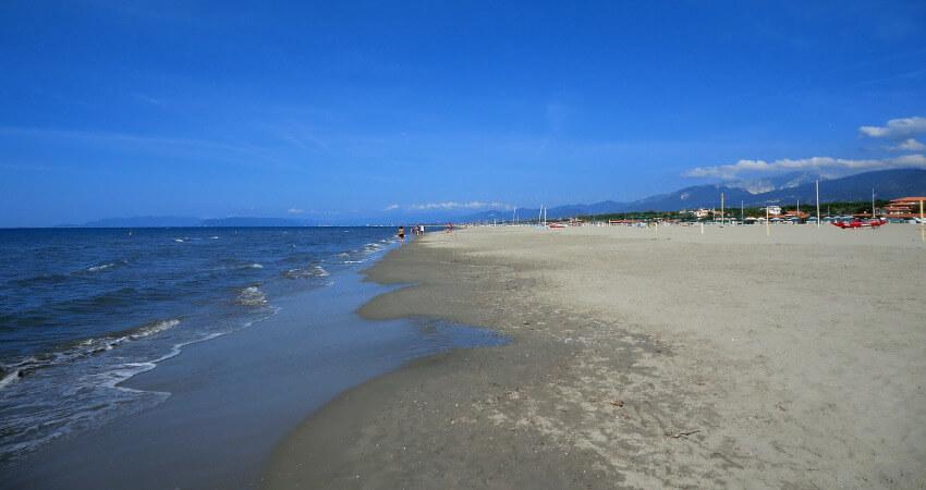 Sandstrand mit klarem Wasser und fast wolkenlosem Himmel.