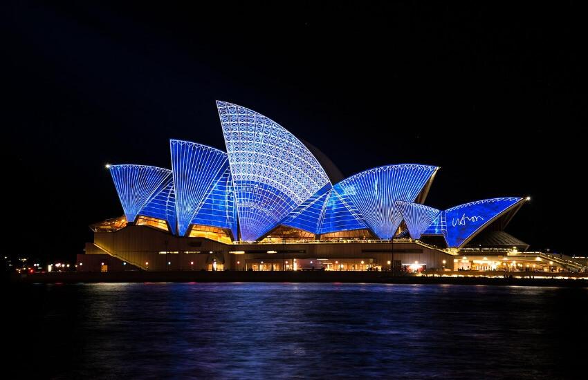 Das Opernhaus von Sydney in der Nacht mit einem kräftigen Blau beleuchtet.