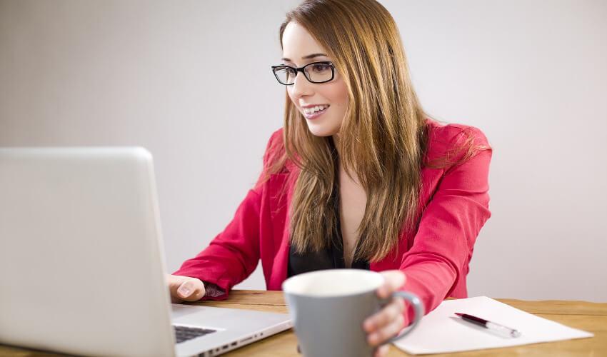 Eine Frau sitzt vor einem Laptop mit einer Tasse Kaffee.