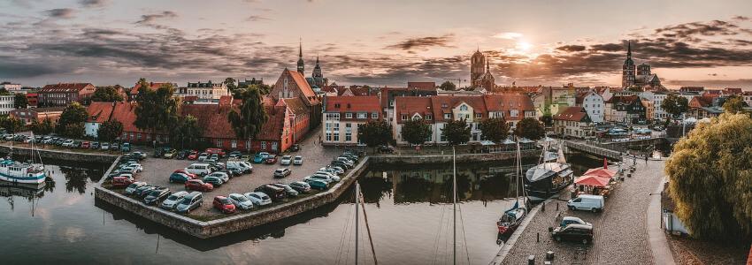 Der Hafen vom Stralsund während des Sonnenuntergangs mit der Altstadt im Hintergrund.