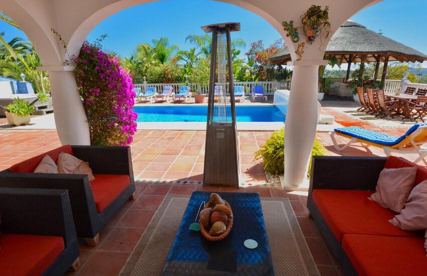 Eine überdachte Terrasse mit Sitzgelegenheiten und Zugang zu einem Pool.