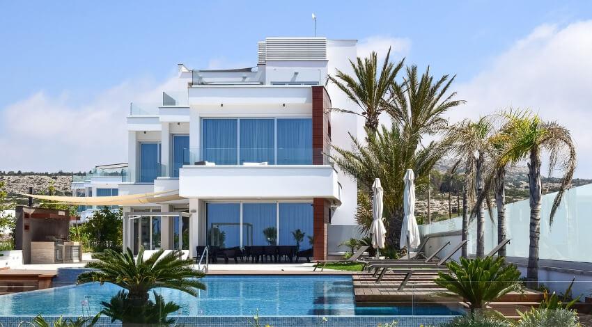 Eine Luxusimmobilie in weiß mit einem Pool davor.