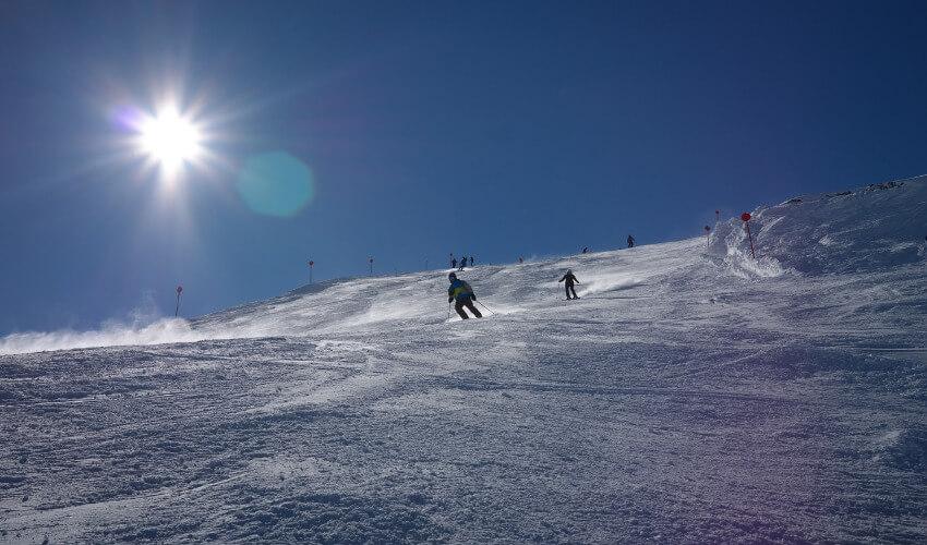 Zwei Skifahrer wedeln eine breite Skipiste hinunter, am Arlberg.