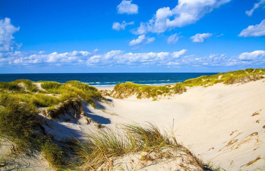 Ein weißer unebener Sandstrand teilweise mit Dünen bewachsen und dahinter das Meer.