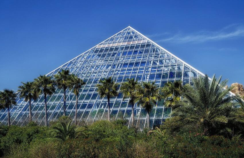 Ein dreieckiges Gebäude mit einer Glasfassade und welches außen mit Sträuchern und Bäumen umgeben ist.