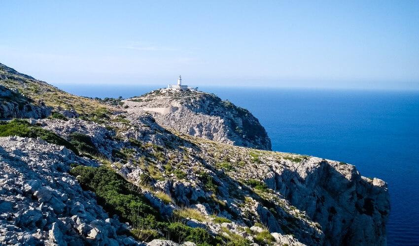 Eine kaum bewachsene Steilküste mit einem Leuchtturm ganz oben.