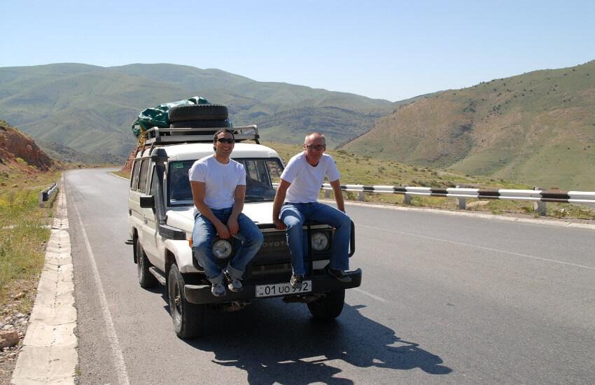 Ein Geländewagen parkt auf der Straße und zwei Männer sitzen auf der Motorhaube.
