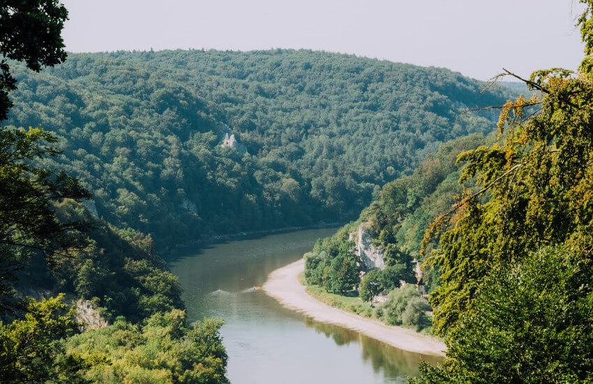 Mit Bäumen bewachsene Hügel, wo sich ein Fluss mit einer Kehre durchgeht.