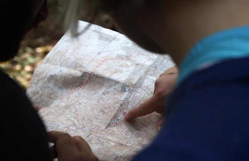 Eine Frau und ein Mann schauen auf eine Landkarte, wobei der Mann einen Punkt mit dem Finger markiert.