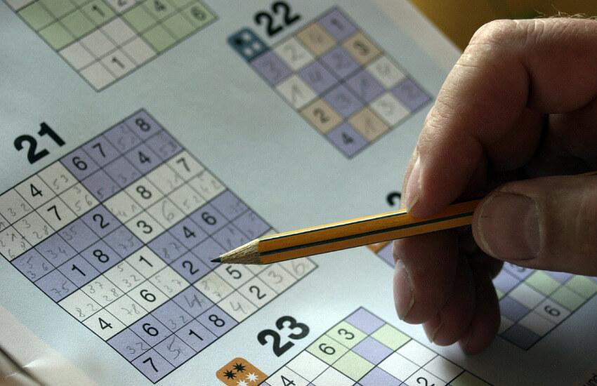 Ein Sudoku Heft, wo eine Hand mit einem Bleistift abgelegt ist.