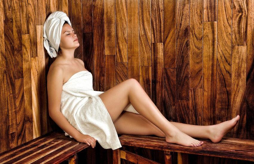 Eine Frau sitzt in einer mit dunklem Holz ausgekleideten Sauna mit einem Handtuch am Körper und einem Handbuch auf dem Kopf.
