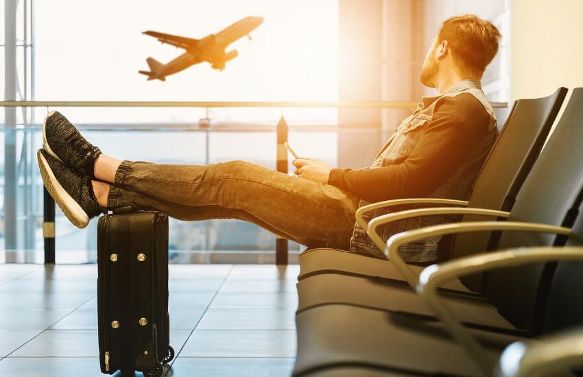 Ein Mann sitzt im Wartebereich eines Flughafens mit den Füßen auf einem Koffer hochgelagert und schaut einem Flugzeug bei Start zu.