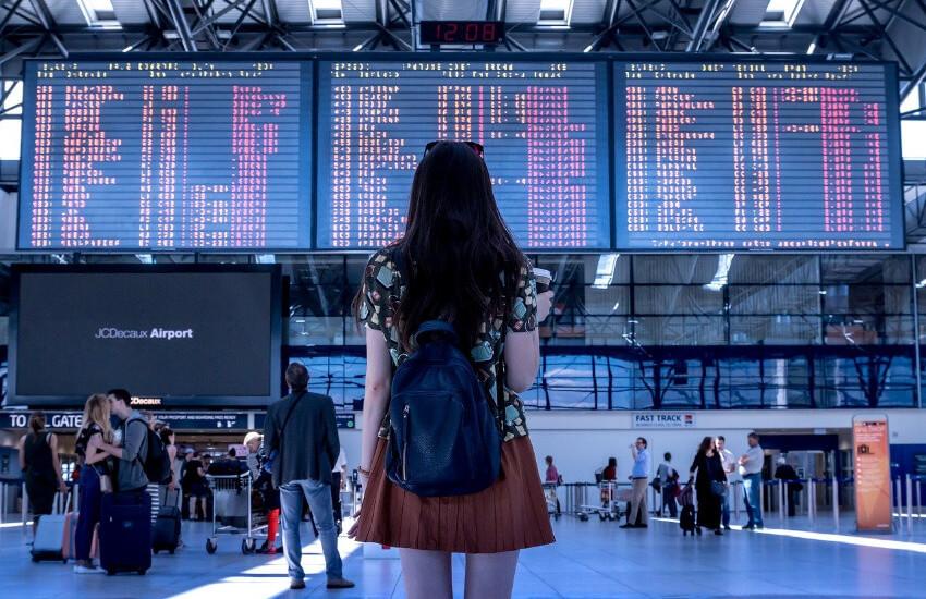 Eine Frau steht in der Abflughalle eines Flughafens und schaut auf die Anzeigentafeln.