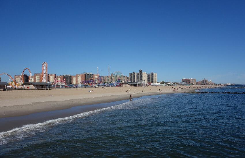 Ein langer Sandstrand am Meer und im Hintergrund ein Vergnügungspark.