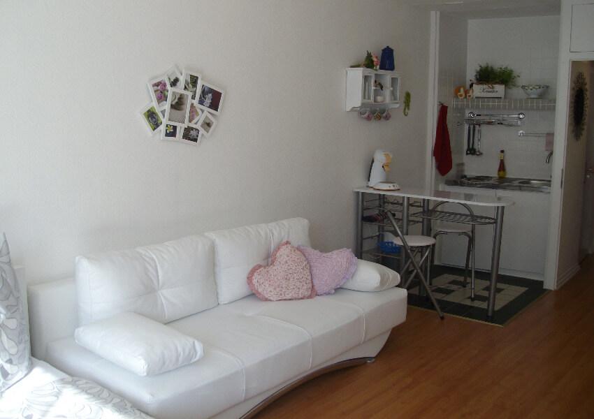Ein Sofa mit einem weißen Bezug Rechts daneben ein kleiner Esstisch und Miniküche.