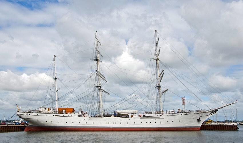 Ein weißes Segelschiff mit 3 hohen Masten.