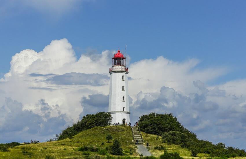Ein weißer Leuchtturm auf einem Hügel, umgeben von Sträuchern und Wiesen.