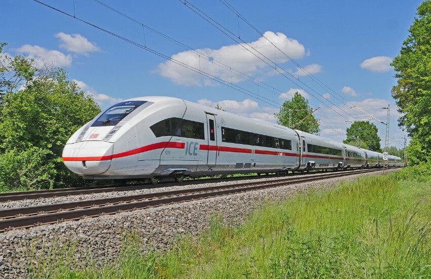 Ein ICE der Deutschen Bahn fährt durch eine unbewohnte Landschaft.
