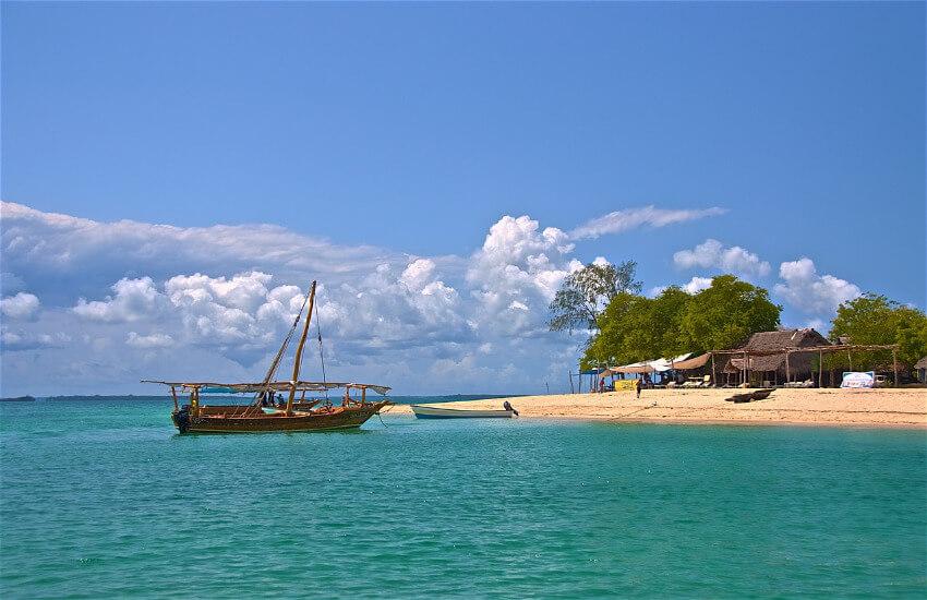 Ein Touristenboot, etwas abgelegen an einem Sandstrand.