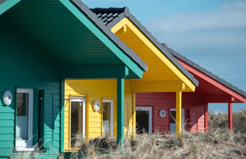Ein grünes, ein gelbes und ein rotes Ferienhaus aus Holz, etwas versetzt zwischen Dünen.