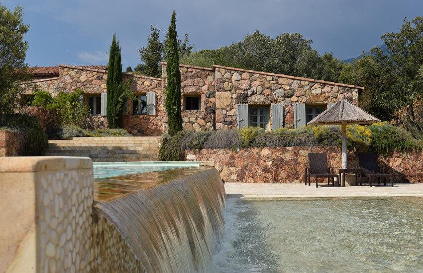 Ein Ferienhaus aus Stein, umgeben von Bäumen und Pflanzen.