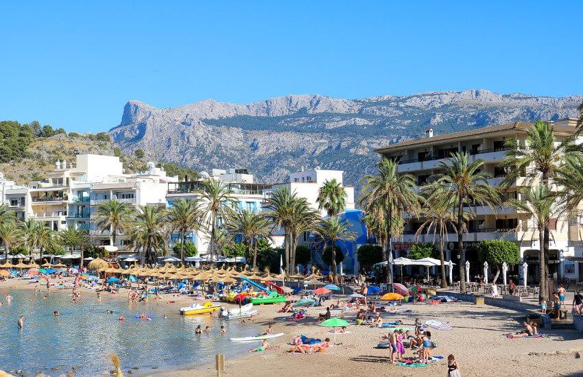 Ein Sandstrand mit vielen Badegästen, dahinter Hotels mit dem Gebirge im Hintergrund.